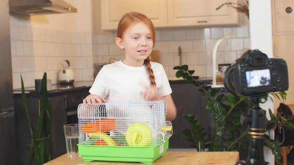 Joyous Red-haired Teen Girl Holding a Rodent Cage Shows It To the Camera, a Teen Blogger. A Long