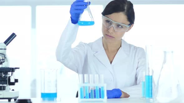 Thumbnail for Scientist Holding and Looking at Blue Solution in Flask