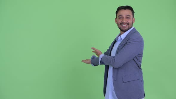 Thumbnail for Happy Young Bearded Persian Businessman Showing To the Back