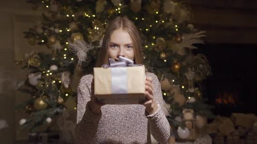 Cute Young Girl Gives a Christmas Present. Holds a Box with a Gift To the Camera and Smiles.