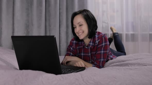 Young Woman Lying on Bed and Having Video Chat Using Webcam on Laptop Computer