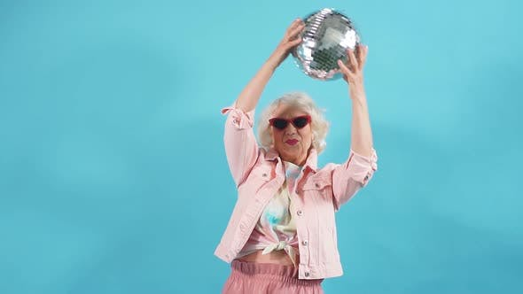 Funny Old Woman in Sunglasses Holding a Ball. Lifestyle, Woman Wants To Dance