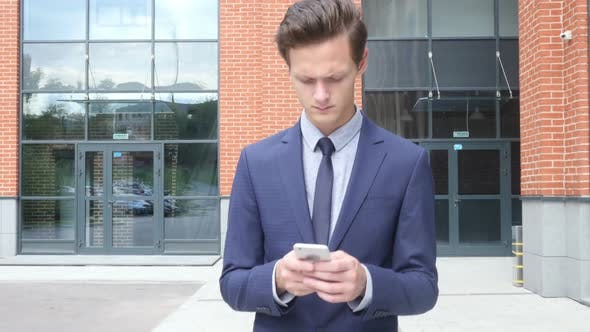 Thumbnail for Walking Businessman Typing Text Message on Smartphone, Email, Outdoor
