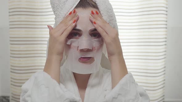 Thumbnail for Cheerful Young Woman looking in the Camera Applying the Sheet Mask on Her Face in the Bathroom