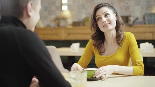 Portrait of Charming Beautiful Caucasian Woman Talking To Unrecognizable Man Sitting in Restaurant