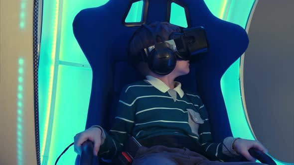 Thumbnail for Male Child in Virtual Reality Chair Enjoying His Experience