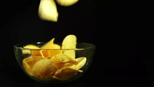 Potato chips falling in a transparent bowl. Dark background