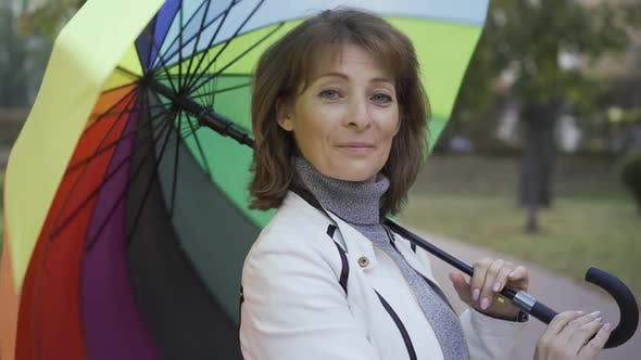 Thumbnail for Confident Caucasian Woman Spinning Multi-colored Umbrella and Smiling. Happy Adult Female Standing