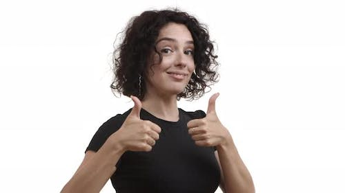 Young Attractive Female Model with Curly Short Hair Showing Thumbsup in Approval and Nodding