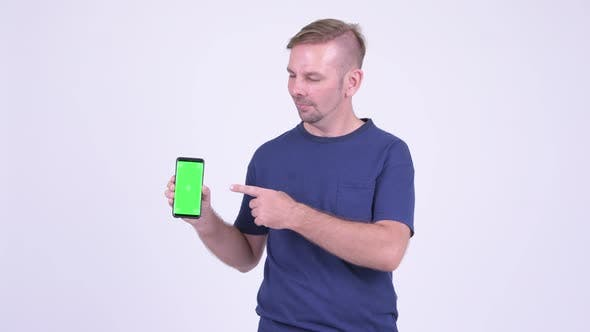 Thumbnail for Portrait of Happy Blonde Man Showing Phone and Giving Thumbs Up