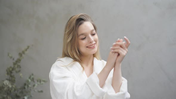 Goodlooking Woman Use Skin Care Products at Home in Light Bathroom
