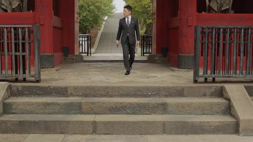Japanischer Geschäftsmann zu Fuß durch ein japanisches Tor