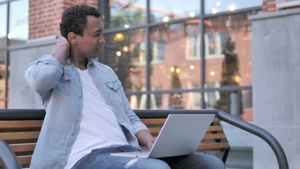 Thumbnail for African Man with Neck Pain Using Laptop Outdoor