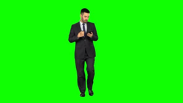 Cover Image for Happy Young Businessman Reads News Messages on a Mobile Phone and Drinks Coffee on Green Background