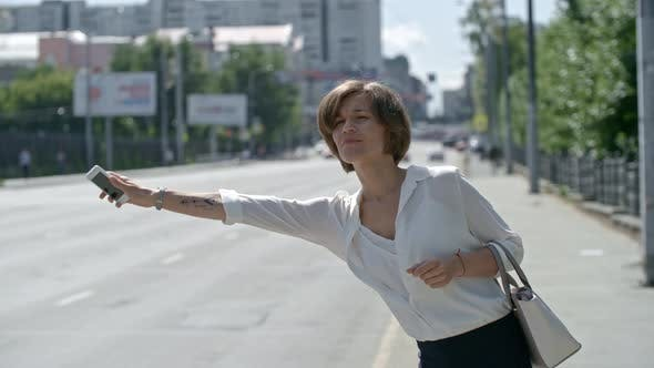 Thumbnail for Businesswoman Using Smart Phone and Hailing Taxi in the Street