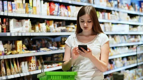 Beautiful Young Woman with Shopping Basket Use Phone in Supermarket, Texting