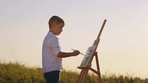 Boy Drawing on Canvas in Open Air