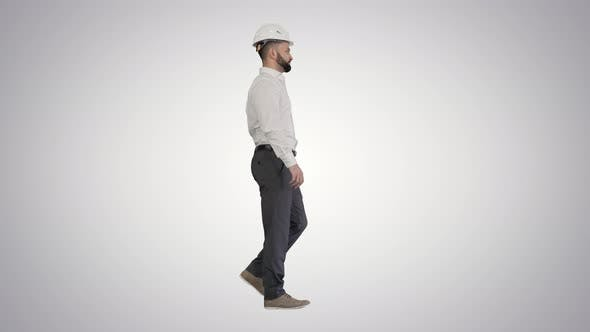 Businessman in Formal Wear and White Hardhat Walking on Gradient Background