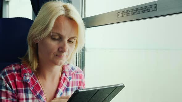 Thumbnail for A Young Woman Is Traveling on a Train. Sits By the Window, Uses a Digital Tablet