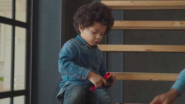 Cover Image for Concentrated Mixed Race Boy Using Toy Wrench