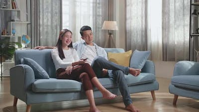 Young Asian Couple Relaxing And Watching Tv At Home