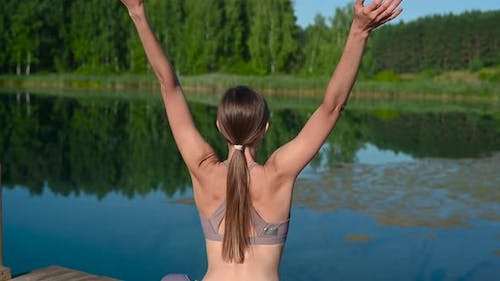 Woman Sitting in Lotus Position and Doing Yoga on a Forest Lake. Beautiful Girl Doing Exercises on