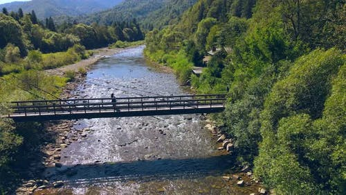 Aerial View From Old Wooden Suspension Bridge Over a Mountain River. Girl Standing on a Wooden