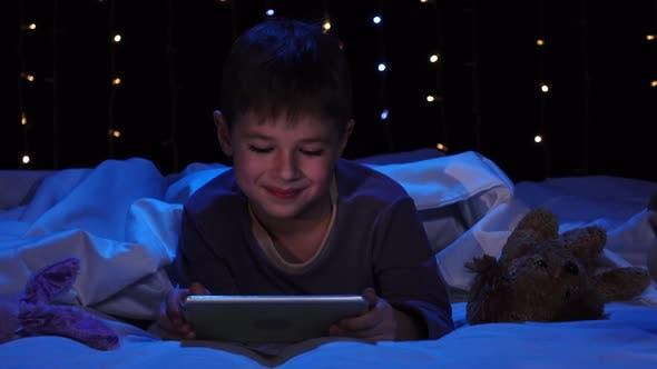 Thumbnail for Kind liegt auf einem Bett, der einen Laptop hält und einen Cartoon beobachtet. Bokeh Hintergrund