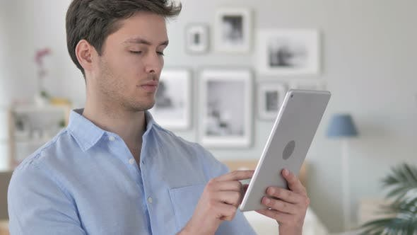 Thumbnail for Handsome Young Man Browsing on Tablet