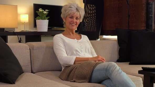 A Friendly Middle-aged Woman Sits on a Couch in an Apartment Living Room and Waves at the Camera