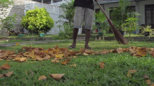 Thumbnail for Dunkelhäutiger Mann in Shorts hält Besen und reinigt trockene Blätter