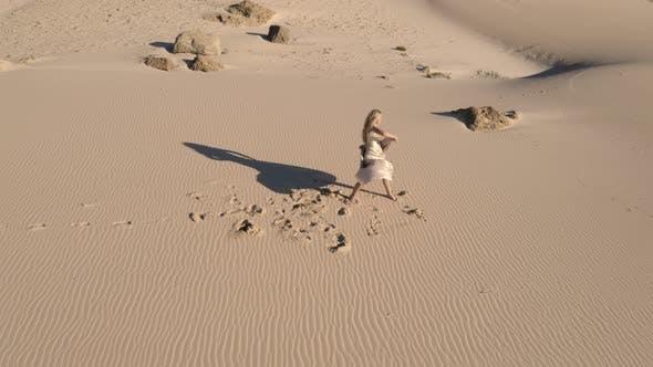 Woman Dancing Barefoot On Beach In Ballgown