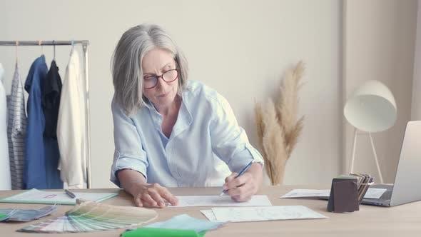 Mature Older Elegant Woman Fashion Designer Drawing Sketches on Table