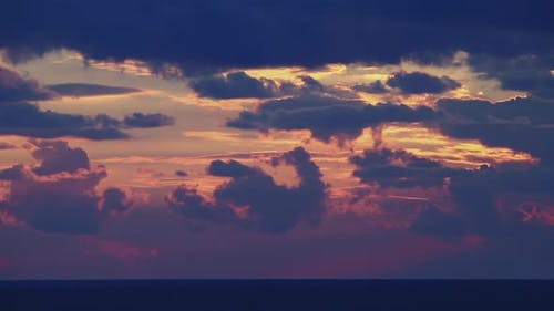 Bright Disk of Sun Moves Through Gapes of Clouds in Shining Sunset Sky