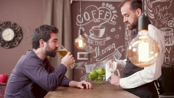 Thumbnail for Young Bearded Man Tells a Story To the Bartender and Drinks Beer
