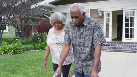 Thumbnail for Mature black couple walking together with walker