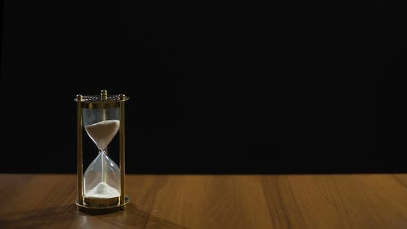 Cover Image for Sand Flowing Fast in Hourglass on Table Against Black Background, Time Flies