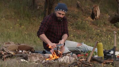 Tourist Sits Near Campfire and Sharpen a Stick with Knife