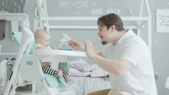 Thumbnail for Caring Dad with Cellphone Feeding Infant Bsaby