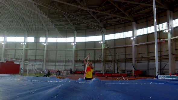 Pole Vaulting - Sportsman in Yellow t Shirt Is Running and Jumping Over the Bar