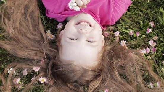 Cover Image for Close-up Smiling Little Cute Baby Girl Lying on Green Grass Holding Flowers Looking at Camera