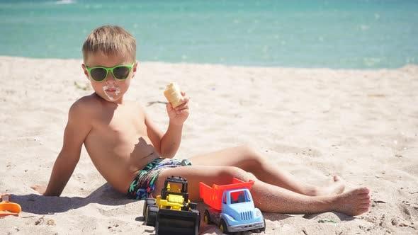 Blonde Boy Eating Ice Cream Sitting on a Sandy Beach