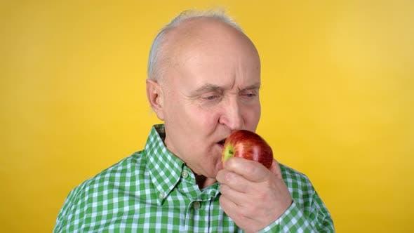 Thumbnail for Elderly Man Eating Red Apple