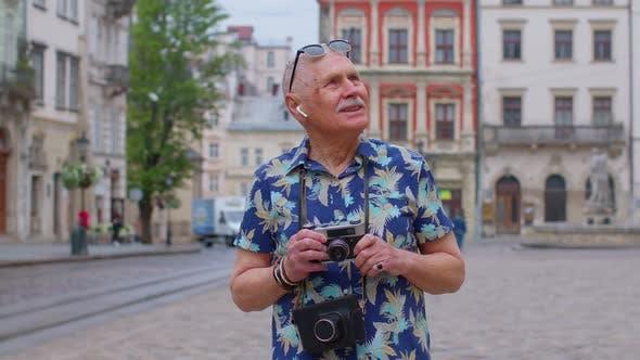 Senior Man Tourist with Retro Photo Camera Smiling Listening Music Earphones Dancing on Street