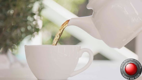 Tea Pouring Into A White Cup From A Pot Outside On A Patio Shot On Red Camera