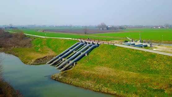Road Bridge Over Water Supply System Pipes on River By Field