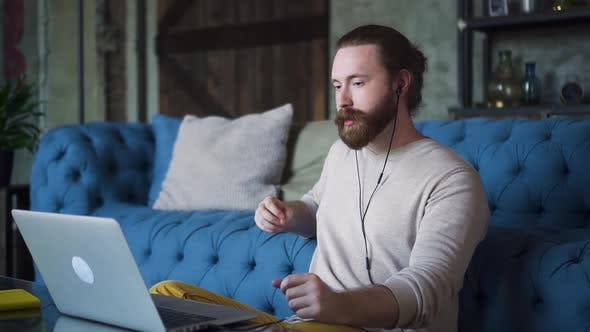Thumbnail for Young Bearded Businessman Discusses Business and Has Online Call on Couch in Apartment Spbd.