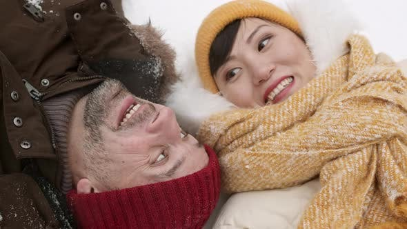 Diverse Couple Lying on Snow