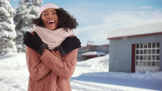 Cover Image for Portrait of cute African American female trying to warm up outside in the snow