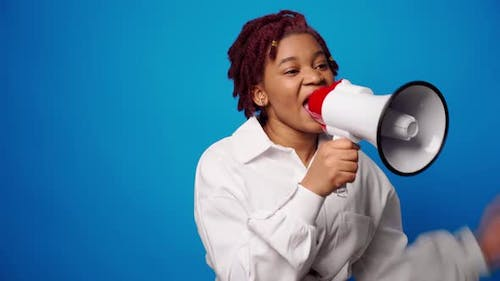 African American Woman Using Megaphone Against Blue Background